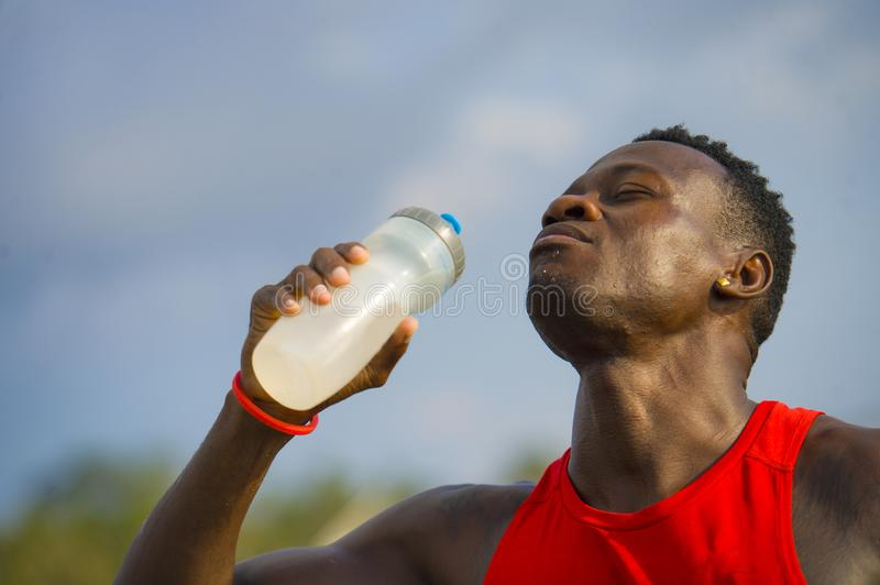 Young handsome and attractive black afro American sport man tired and thirsty after running workout holding bottle drinking water. Or isotonic energy drink stock photos