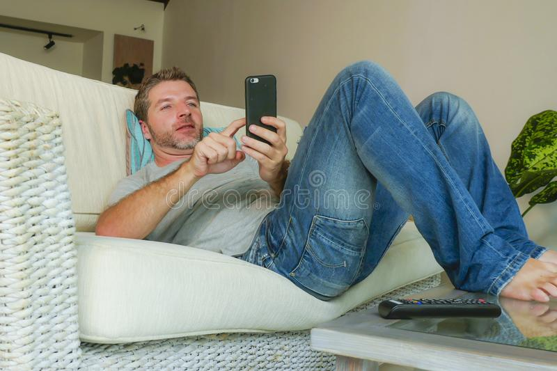 Young handsome attractive happy man using online dating app on mobile phone networking with smartphone lying at home couch. Lifestyle indoors portrait of young stock photo