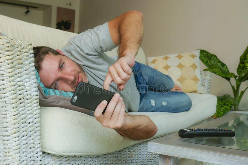 Young handsome attractive happy man using online dating app on mobile phone networking with smartphone lying at home couch. Lifestyle indoors portrait of young royalty free stock photo