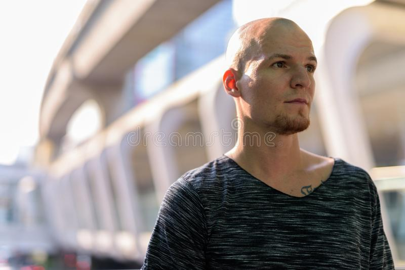 Young handsome bald man thinking against exterior of the mall in royalty free stock photos