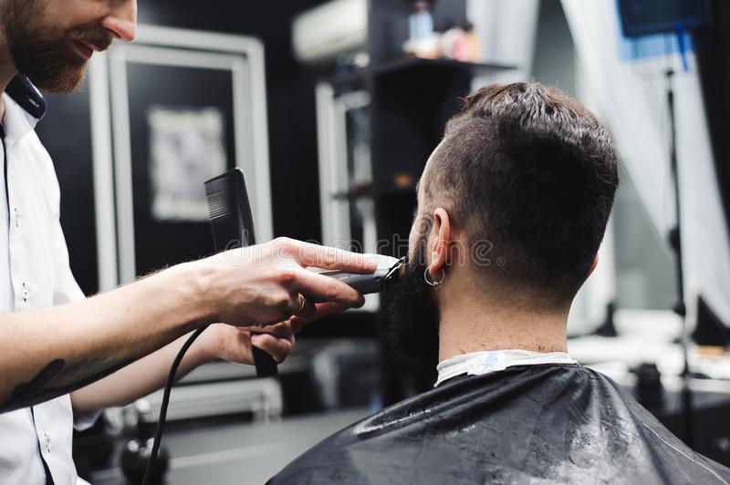 Young handsome barber making haircut of attractive man in barbershop. Young handsome barber making haircut of attractive men in barbershop royalty free stock photos