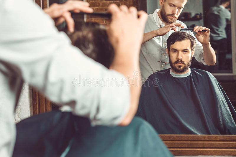 Young handsome barber making haircut of attractive man in barbershop stock image