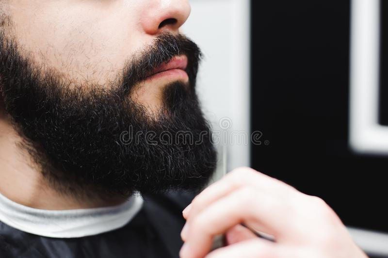 Young handsome barber making haircut of attractive man in barbershop. royalty free stock photo