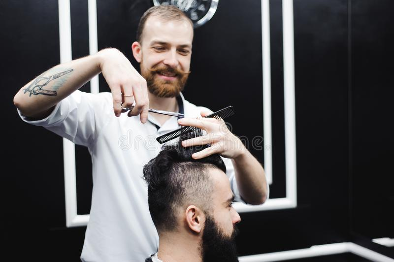 Young handsome barber making haircut of attractive man in barbershop. stock photos