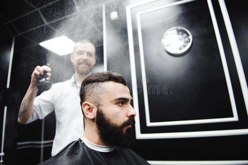 Young handsome barber making haircut of attractive man in barbershop. Young handsome barber making haircut of attractive men in barbershop stock photo