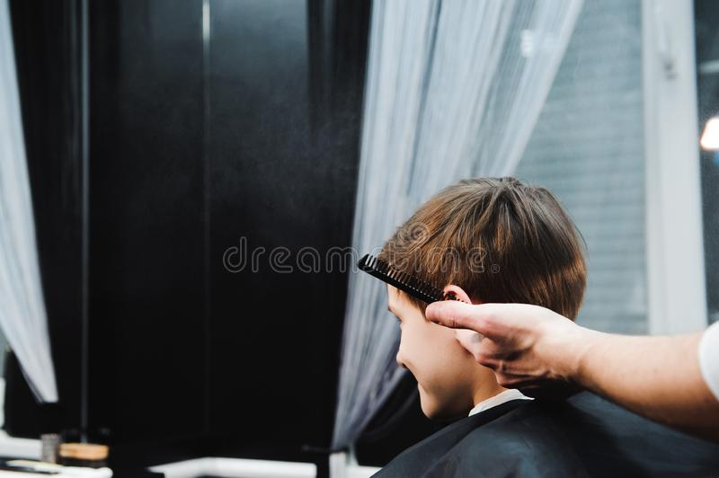 Young handsome barber making haircut of cute boy in barbershop. Young handsome barber making haircut of cute boy in barbershop royalty free stock image