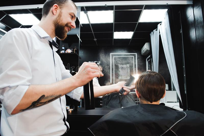 Young handsome barber making haircut of cute boy in barbershop. stock photo