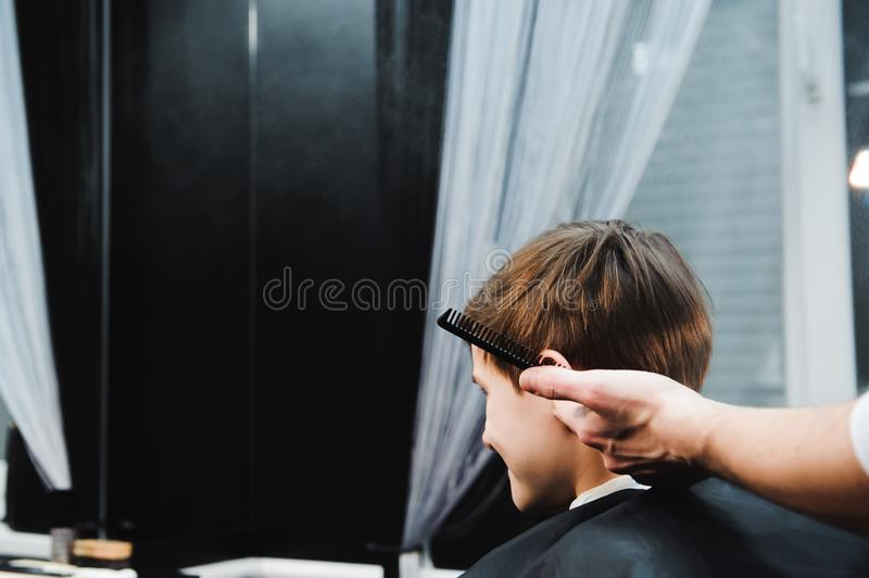 Young handsome barber making haircut of cute boy in barbershop.  stock photography