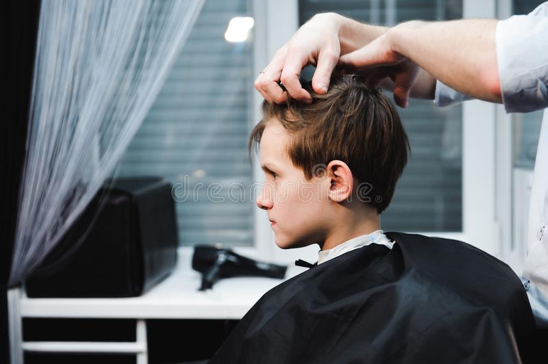 Young handsome barber making haircut of cute boy in barbershop.  royalty free stock photography