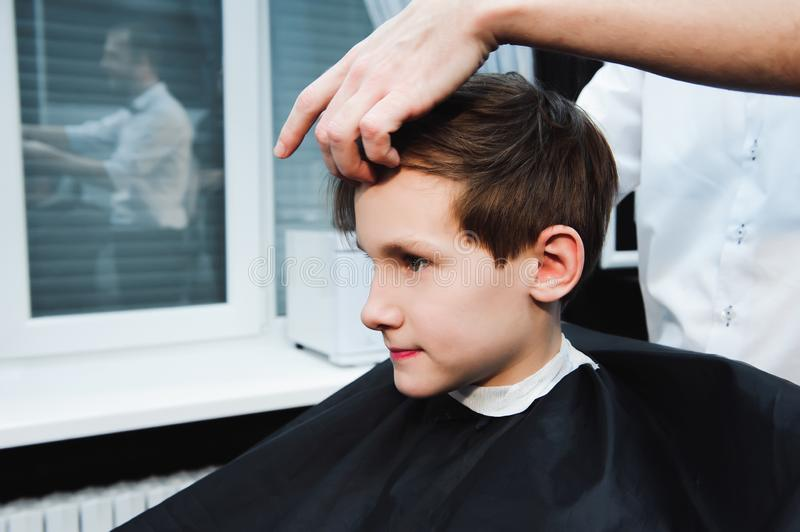 Young handsome barber making haircut of cute boy in barbershop.  royalty free stock images