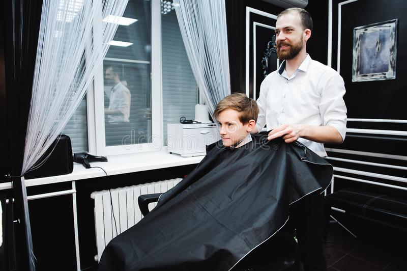 Young handsome barber making haircut of cute boy in barbershop. stock photos