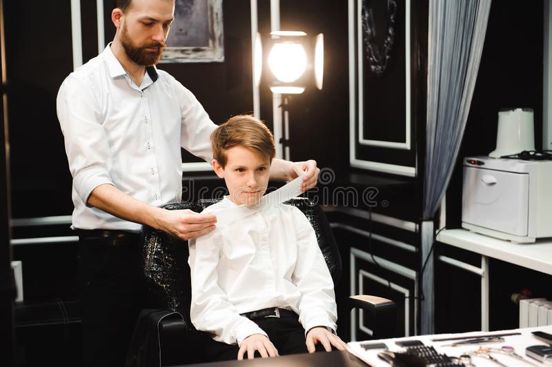 Young handsome barber making haircut of cute boy in barbershop. Young handsome barber making haircut of cute boy in barbershop stock photo
