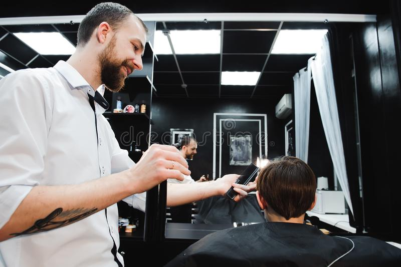 Young handsome barber making haircut of cute boy in barbershop. Young handsome barber making haircut of cute boy in barbershop royalty free stock photo