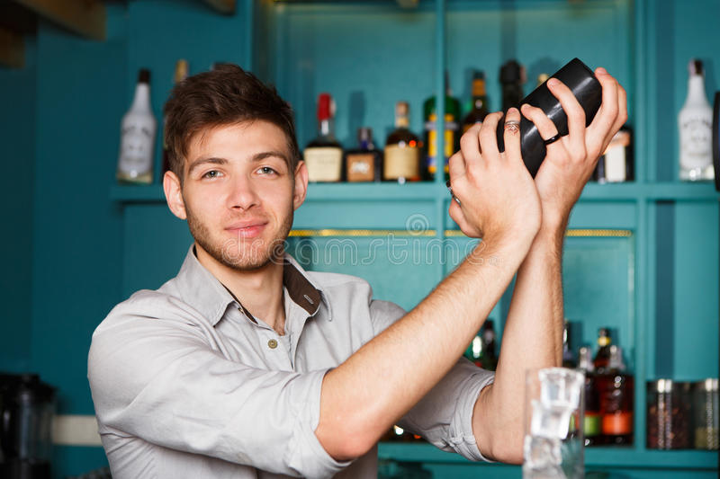 Young handsome barman in bar shaking and mixing alcohol cocktail royalty free stock photos