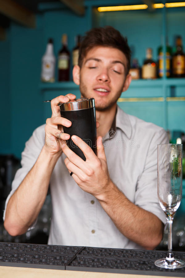 Young handsome barman in bar shaking and mixing alcohol cocktail stock photography