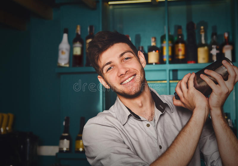 Young handsome barman in bar shaking and mixing alcohol cocktail stock photo