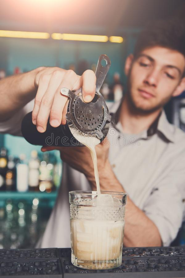 Young bartender pouring cocktail drink into glass royalty free stock photo