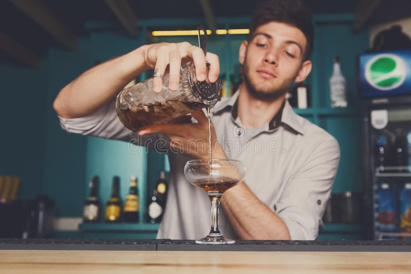Young bartender pouring cocktail drink into glass royalty free stock photos