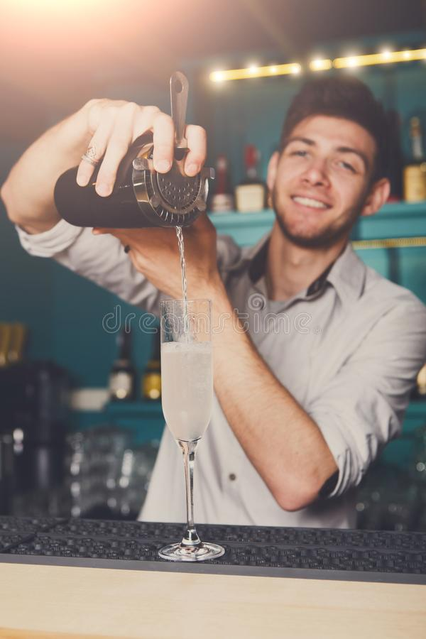 Young bartender pouring cocktail drink into glass stock images