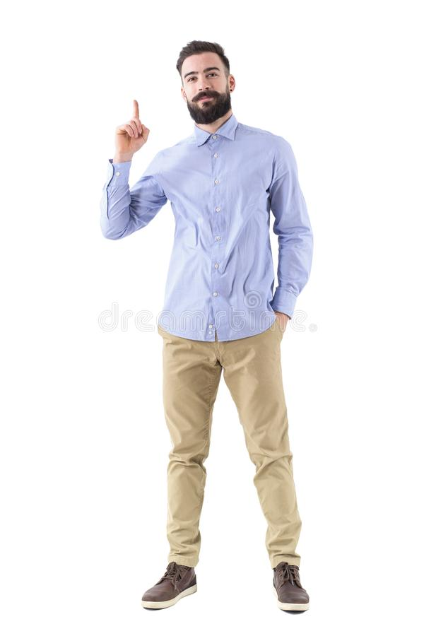 Young handsome bearded business man having idea pointing finger up in smart casual wear. Full body length portrait isolated on white background royalty free stock photos