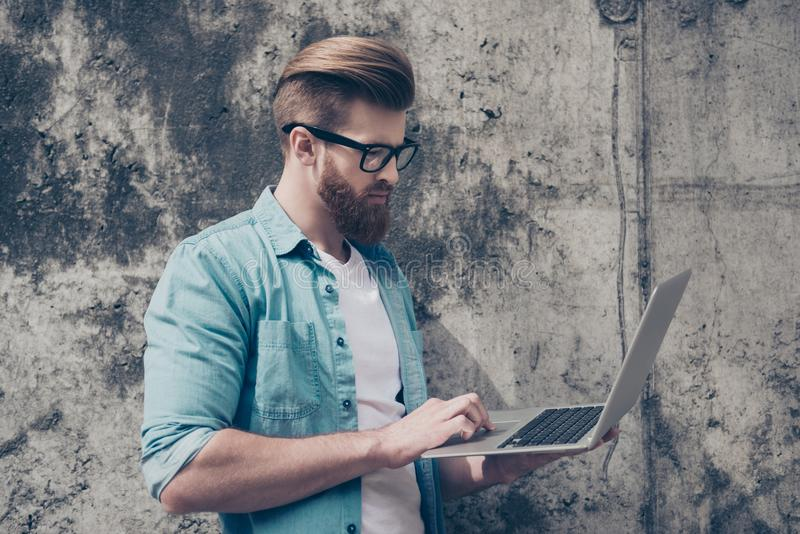 Young handsome bearded entrepreneur is working outdoors on his l. Aptop. Very stylish and trendy royalty free stock images