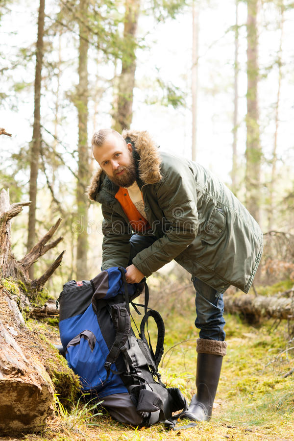 Young, handsome bearded guy stopped for a break in forest. Camp, tourism, hiking concept royalty free stock image