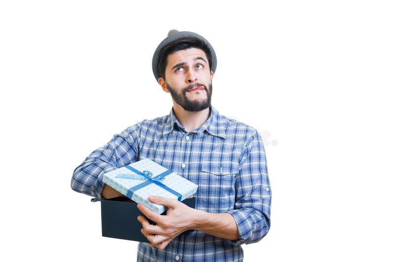 Bearded guy with gift. Young handsome bearded hipster holding gift box in hands royalty free stock images