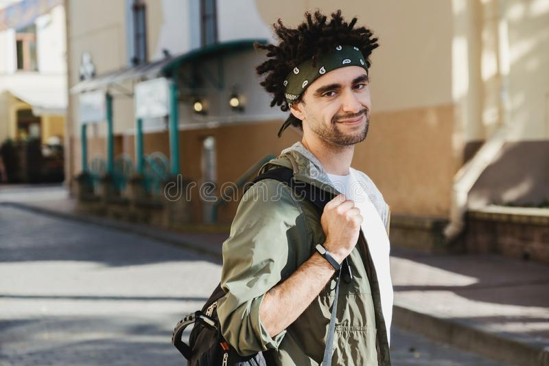 Young handsome bearded man with dreadlocks hairstyle looking at camera, outdoor hipster portrait on the autumn European street. royalty free stock image