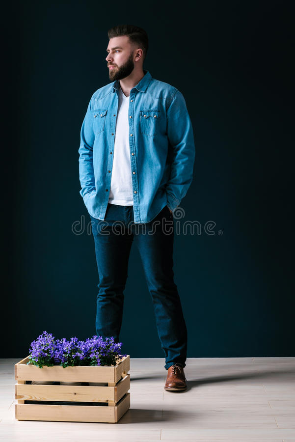 A young handsome bearded man, dressed in a denim shirt and blue trousers, stands indoors stock photography