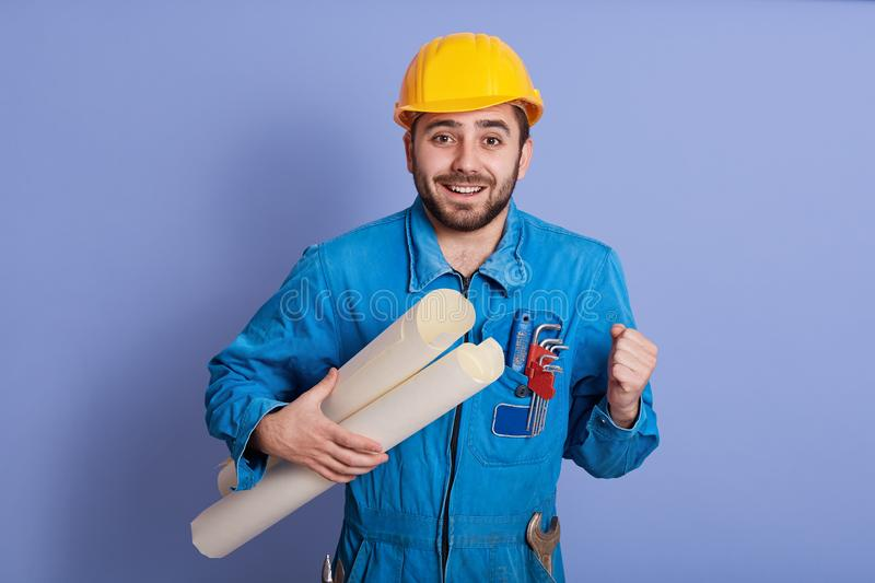 Young handsome bearded man engineer, architect holding rolled up technical drawing, looks happy, celebrating succses of new royalty free stock images