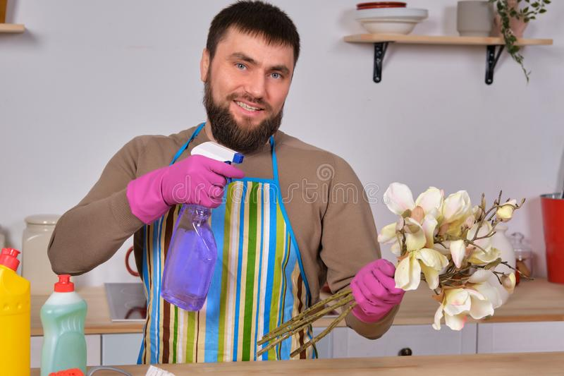 Young handsome bearded man in the kitchen, shows all his cleaning staff - detergents, brushes, sprays. He think he is royalty free stock photo