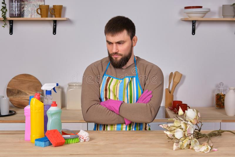 Young handsome bearded man in the kitchen, shows all his cleaning staff - detergents, brushes, sprays. He think he is stock photography