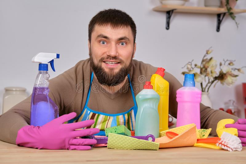 Young handsome bearded man in the kitchen, shows all his cleaning staff - detergents, brushes, sprays. He think he is royalty free stock photography