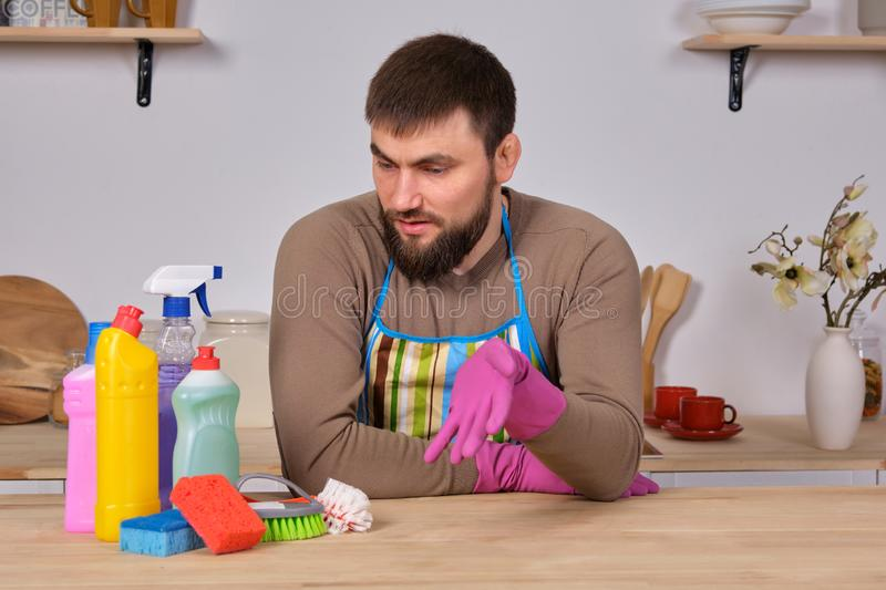 Young handsome bearded man in the kitchen, shows all his cleaning staff - detergents, brushes, sprays. He think he is stock image