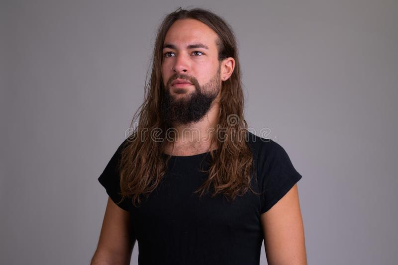 Young handsome bearded man with long hair thinking stock photography