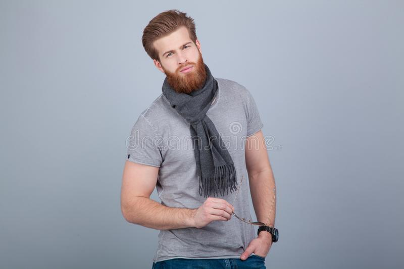 Young handsome bearded man standing by the grey wall wearing scarf and grey t-shirt and holding sunglasses in his hand stock images