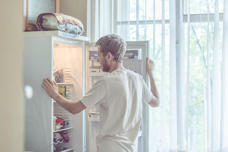 Young handsome bearded man standing near opended fridge at home kitchen royalty free stock image