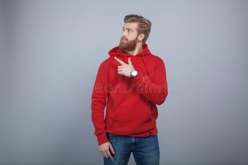 Young handsome bearded man wearing red sweatshirt standing on the grey background and pointing his finger on the left stock image