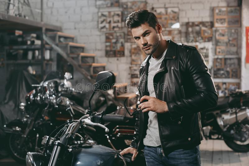 young handsome biker in black leather jacket with classic motorbike stock photos