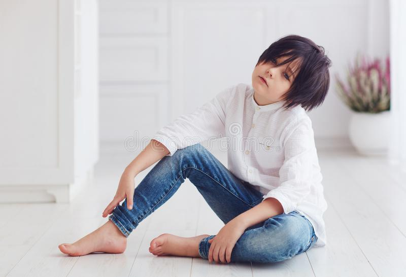 Young calm boy, anime character, sitting barefoot on the floor. Young handsome boy, anime character, sitting barefoot on the floor royalty free stock image