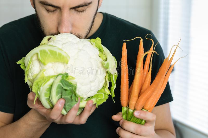 Young handsome brunette man holding fresh vegetables in his hands. With pleasure sniffing cauliflower royalty free stock photo