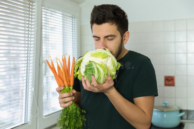 Young handsome brunette man holding fresh vegetables in his hands. With pleasure sniffing cauliflower royalty free stock photos