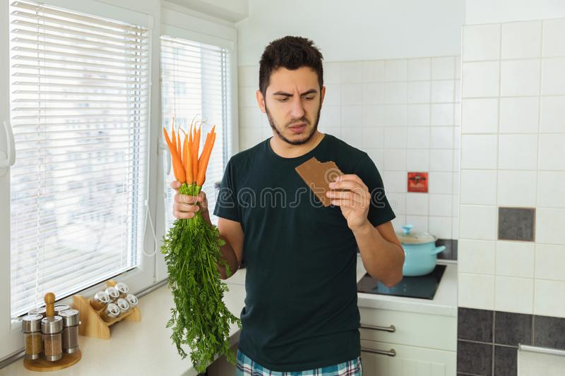 A young handsome brunette man looks at chocolate with disdain and disgust. The man began to lead a healthy lifestyle royalty free stock image