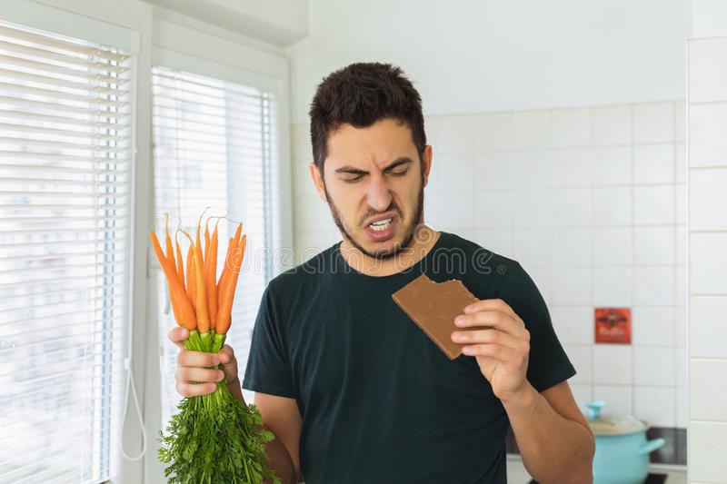 A young handsome brunette man looks at chocolate with disdain and disgust. The man began to lead a healthy lifestyle stock photography