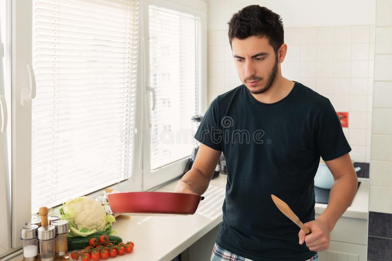 A young handsome brunette man is standing in the kitchen and holding a frying pan in his hands. Husband preparing breakfast for his wife royalty free stock images