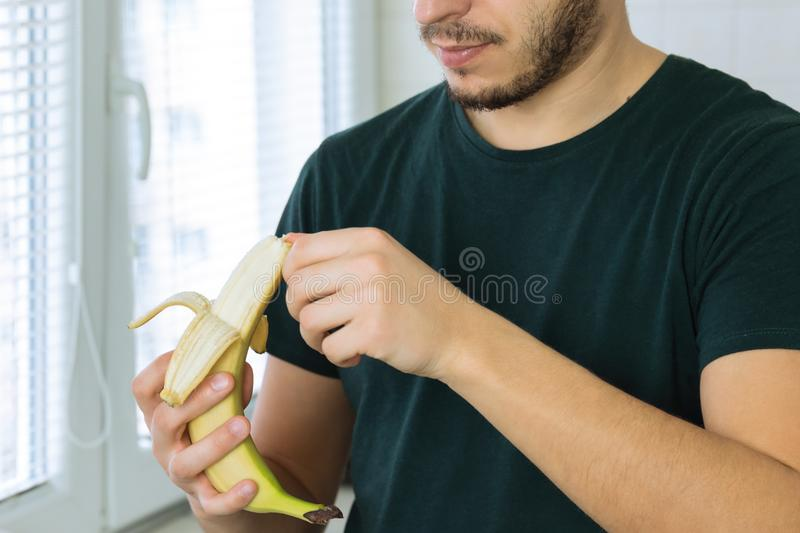 A young handsome brunette man is standing in the kitchen. At home and cleans a banana stock images