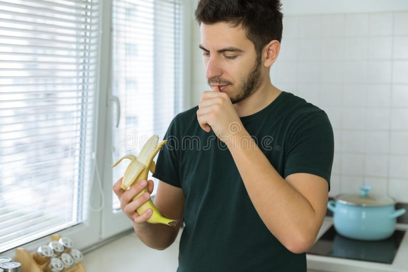 A young handsome brunette man is standing in the kitchen. At home and cleans a banana royalty free stock photo