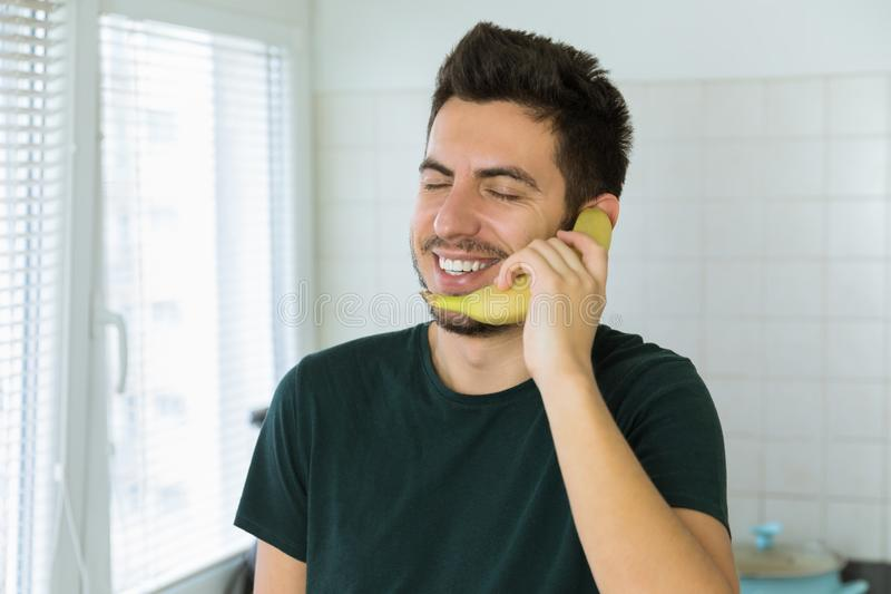 A young handsome brunette man is talking on the phone, instead of using a banana. Conceptual photo photo about dependence on social networks royalty free stock photos