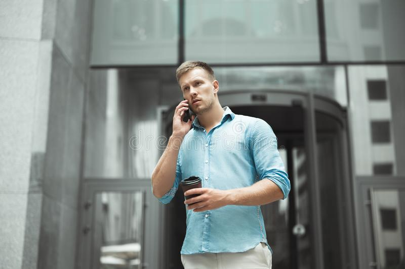 Young handsome business man holding cup of coffee talking on the phone standing near entrance to office business center royalty free stock image