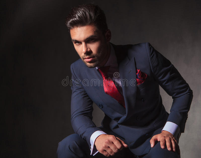 Young handsome business man looking at the camera. While sitting on studio background royalty free stock images